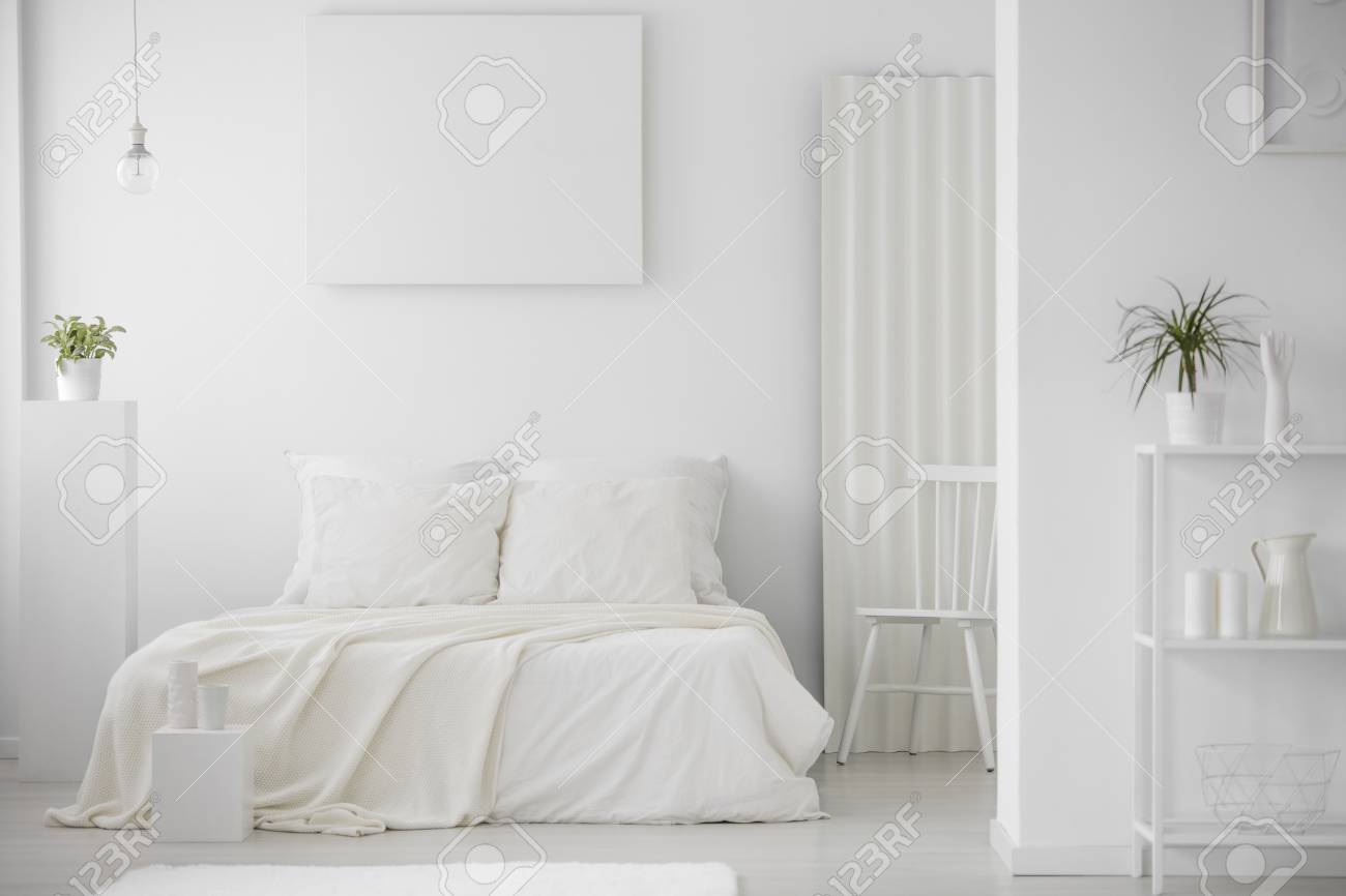 Simple, minimal, white bedroom interior with a large bed, chair,..