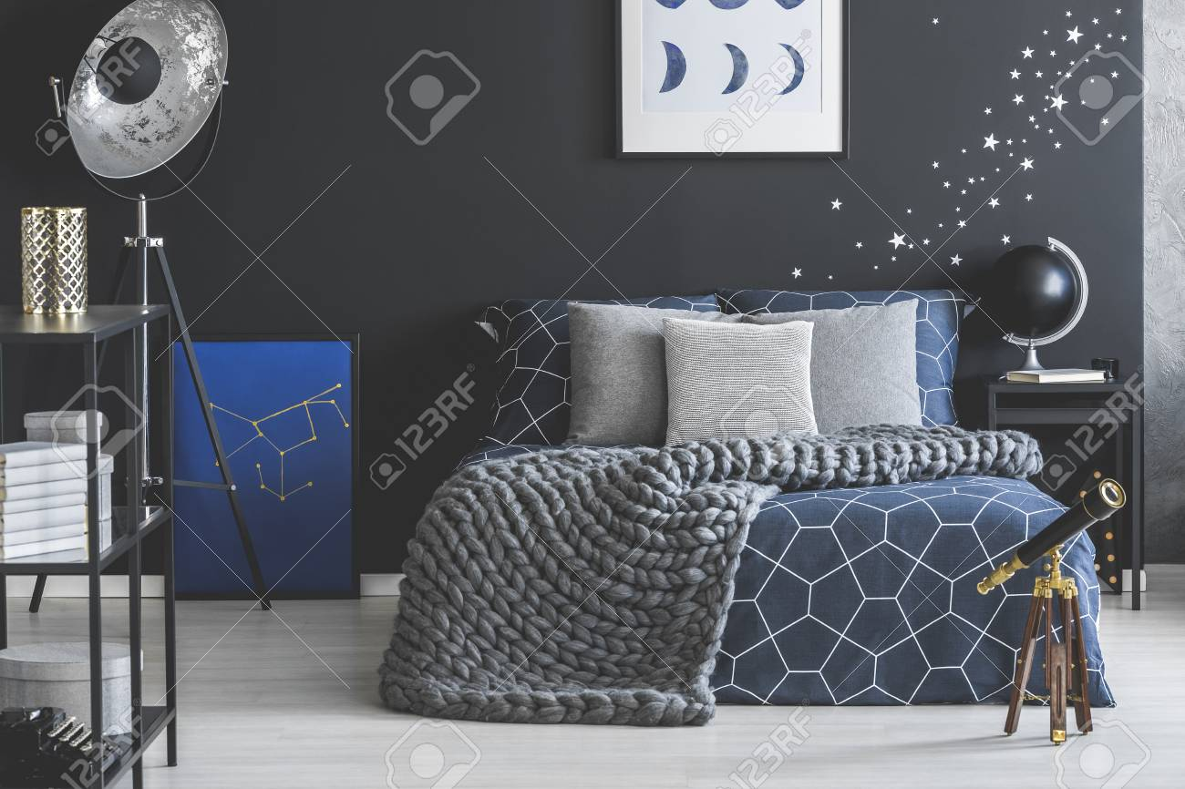 Grey And Blue Bed In Spacious Dark Bedroom Interior With Black