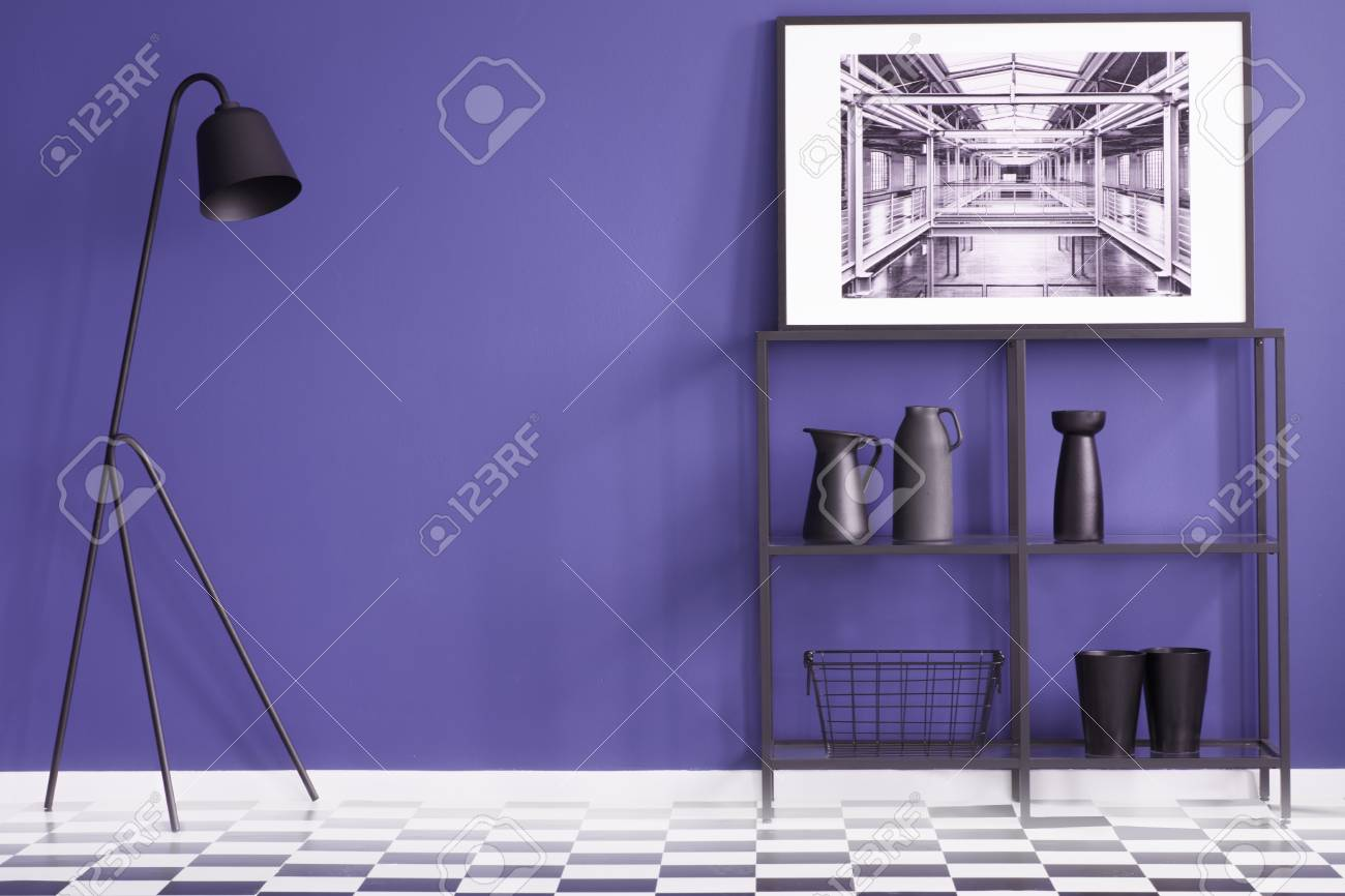 Purple living room with black furniture standing on a checkered..