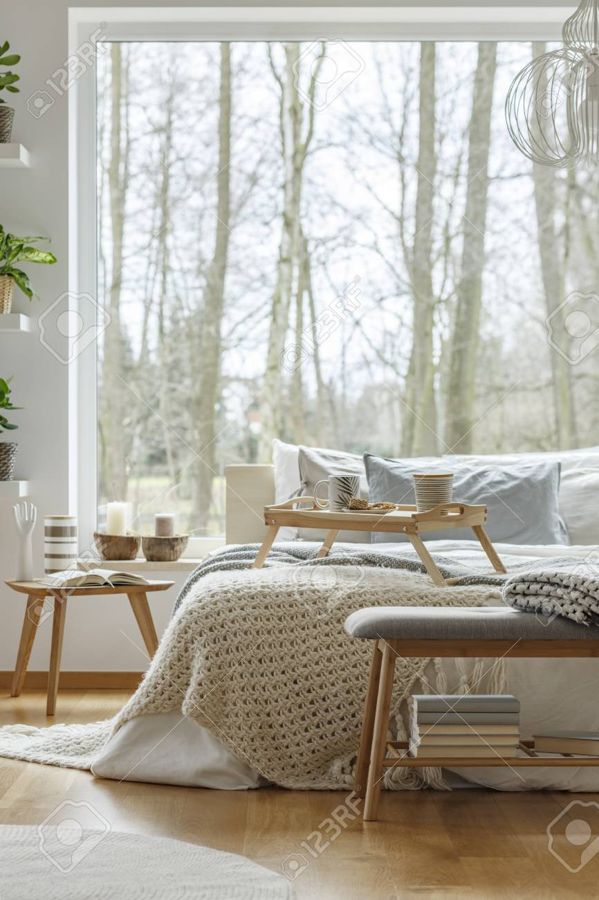 Knit blanket on bed next to wooden table against the window in natural bedroom interior of
