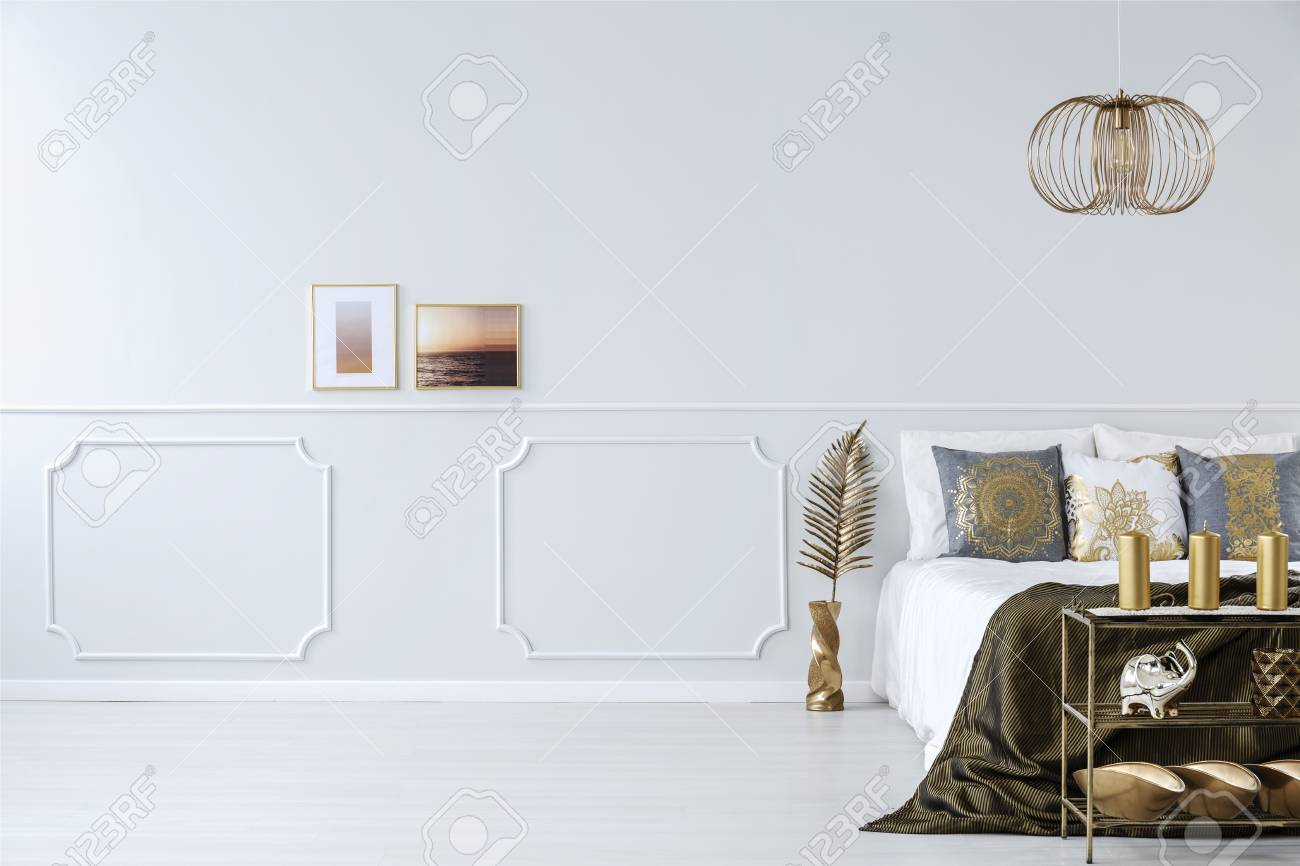Framed Photos On A White Empty Wall In An Elegant Design Bedroom