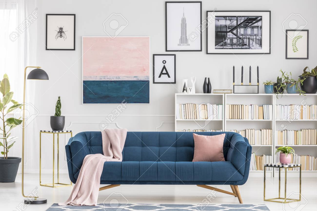 Pink blanket on navy blue sofa in modern living room interior..