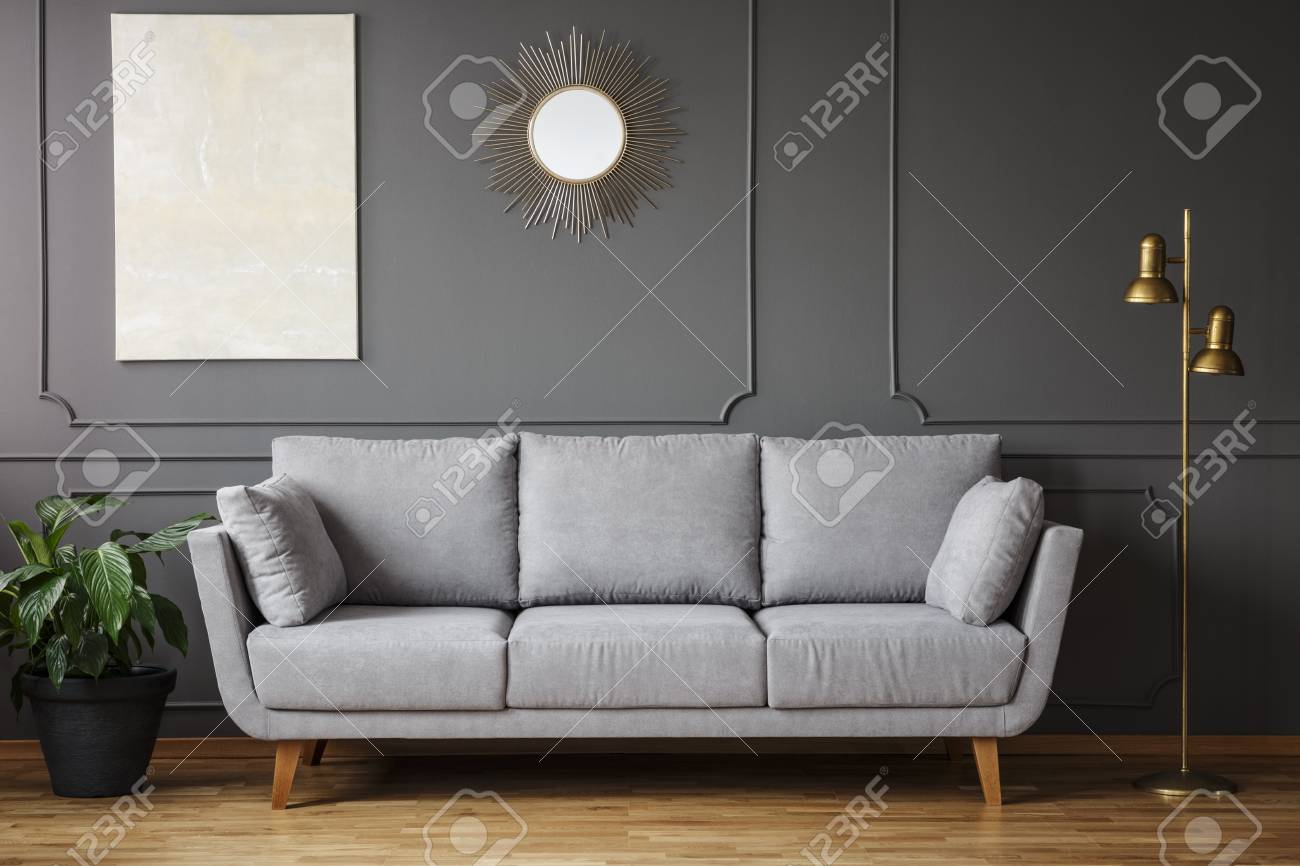 Decorative mirror and modern painting hanging on the wall with molding in dark grey living room interior with fresh plant, gold lamp and bright sofa - 101345144