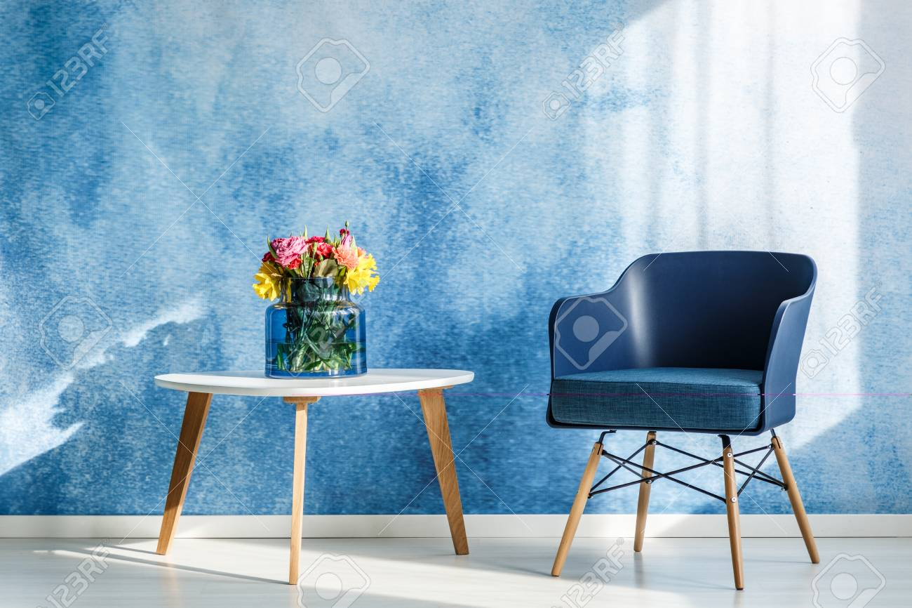 Colorful flowers on white wooden table next to navy blue armchair in simple living room interior