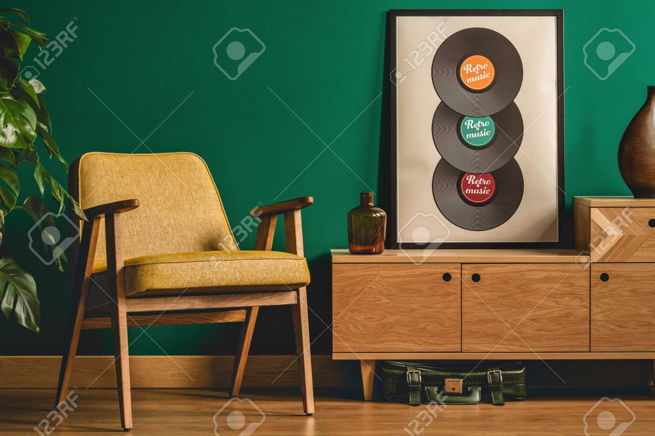 photo vintage armchair wooden cabinet and poster with vinyl records in living room interior
