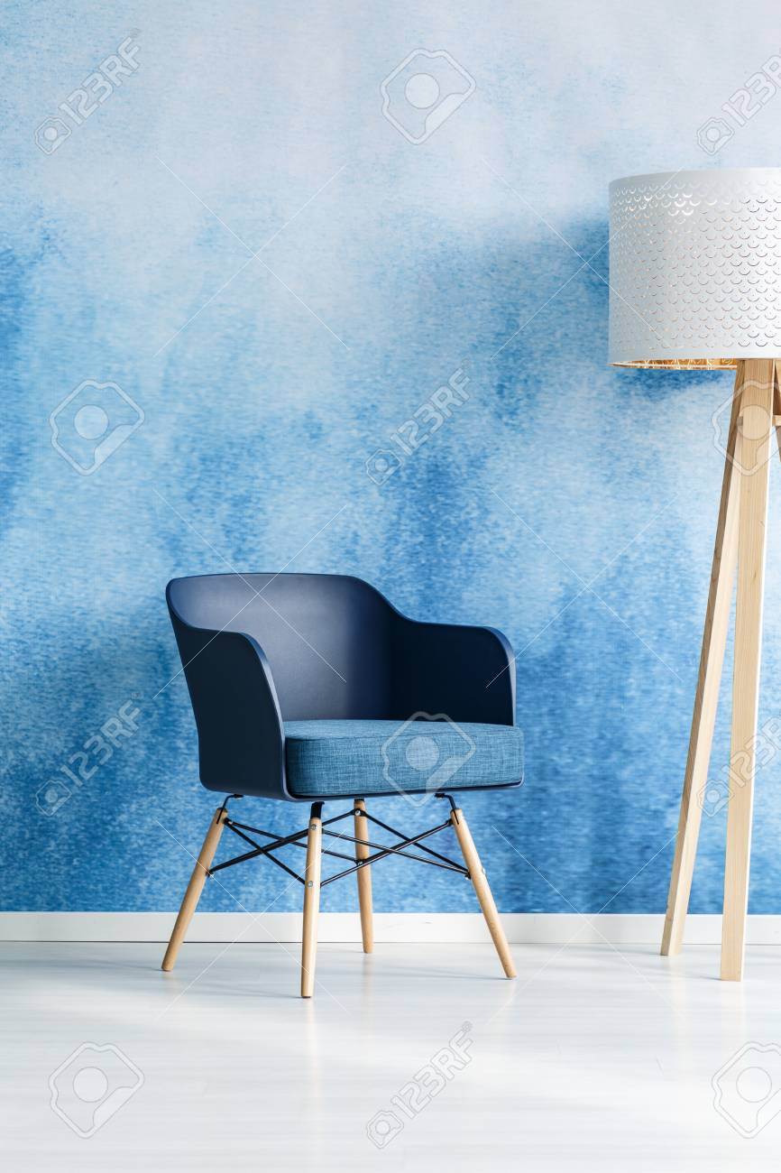 Navy blue armchair next to white wooden lamp in modern living room interior with ombre wall