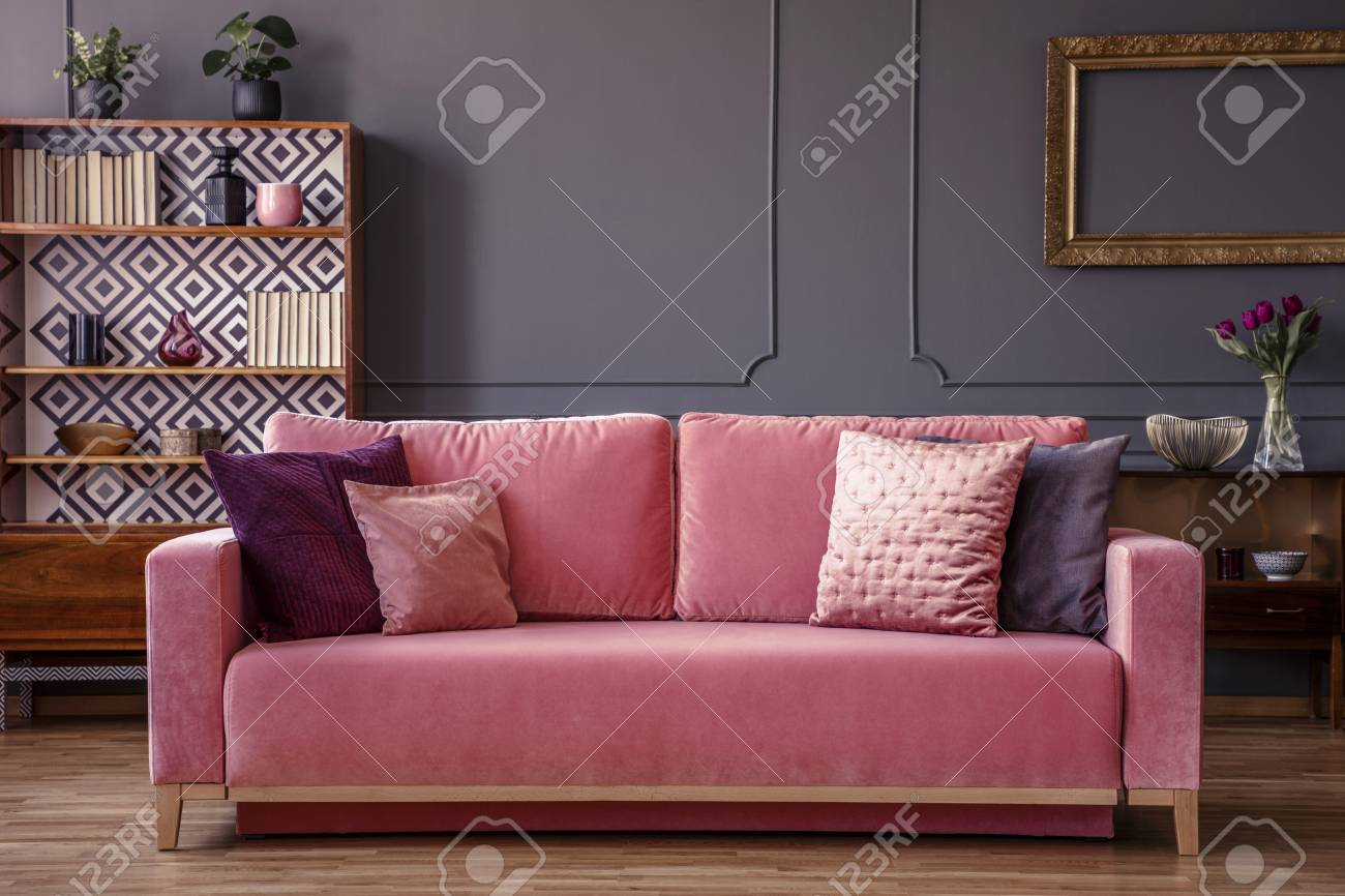 Pink Velvet Couch With Decorative Pillows Standing In Grey Living