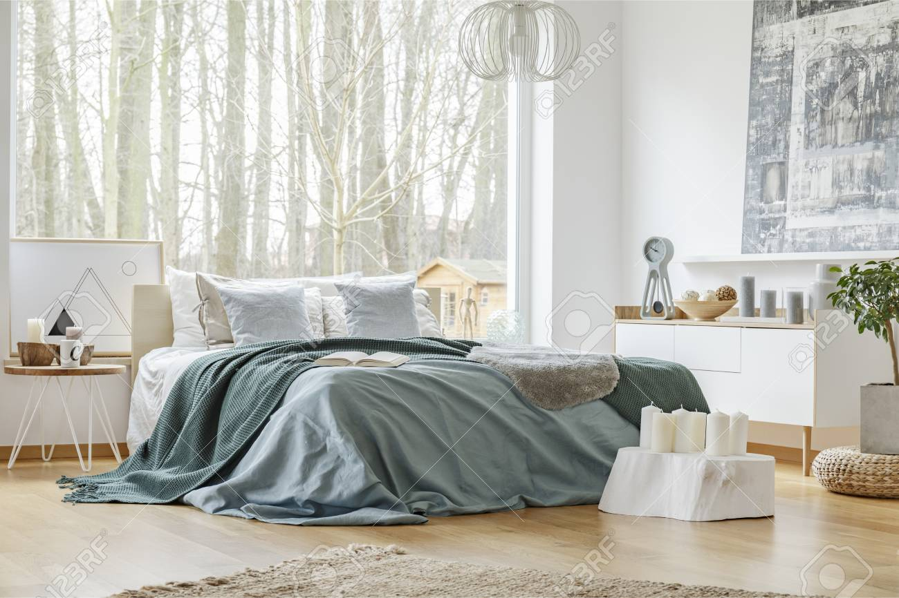 Green And Blue Bedsheets On Bed In Bright Bedroom Interior With Stock Photo Picture And Royalty Free Image Image 101304013