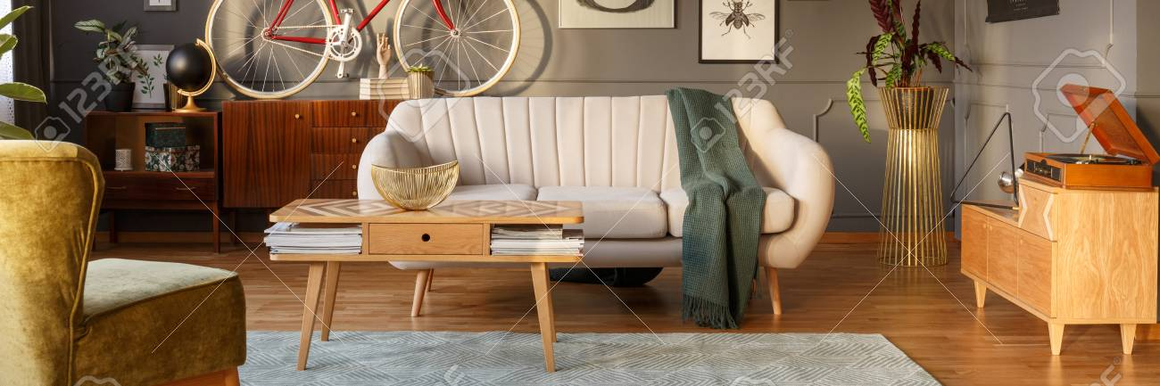 Light grey sofa with green blanket placed in dark grey living..