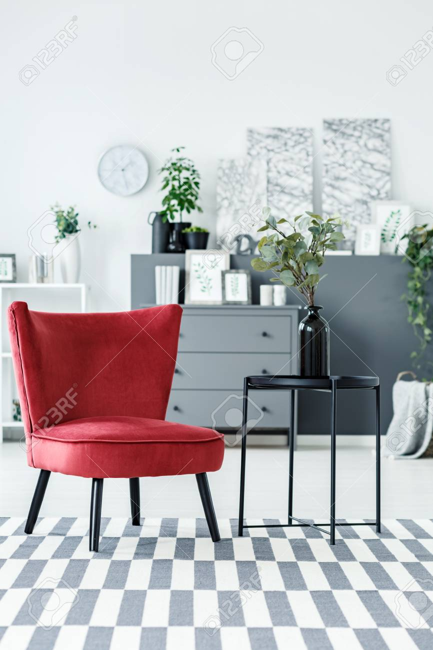 Burgundy Armchair, Black Side Table And Patterned Rug In A Living ...