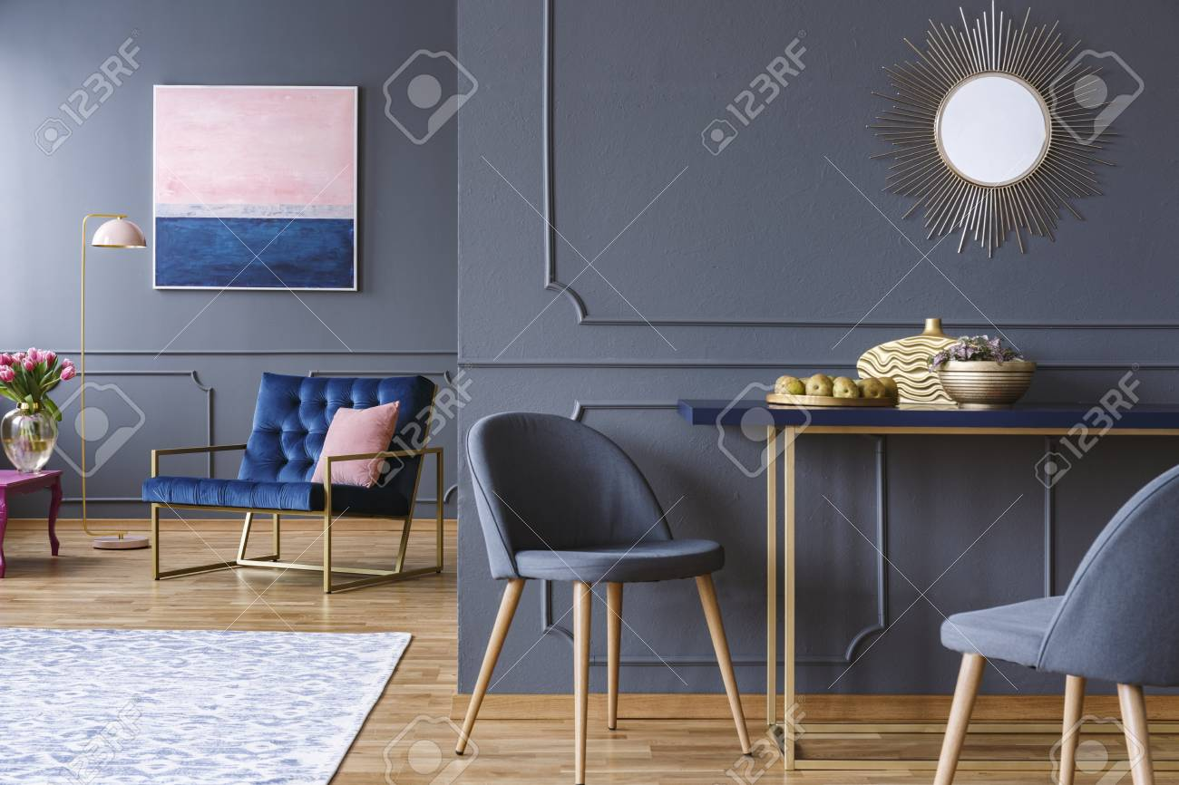 Chair at table in modern grey apartment interior with navy blue armchair painting and mirror