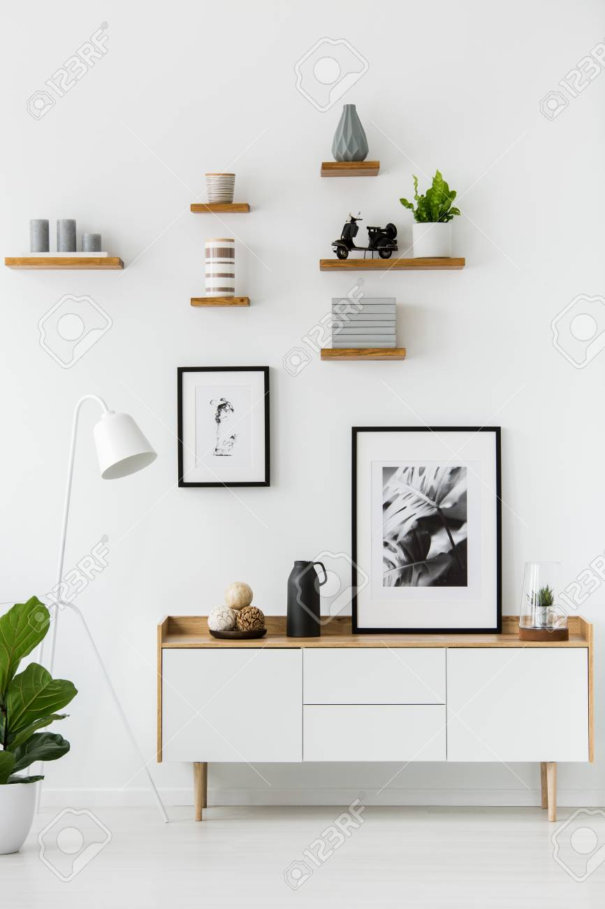 Poster on wooden cupboard in white living room interior with lamp and plant. Real photo - 101667628