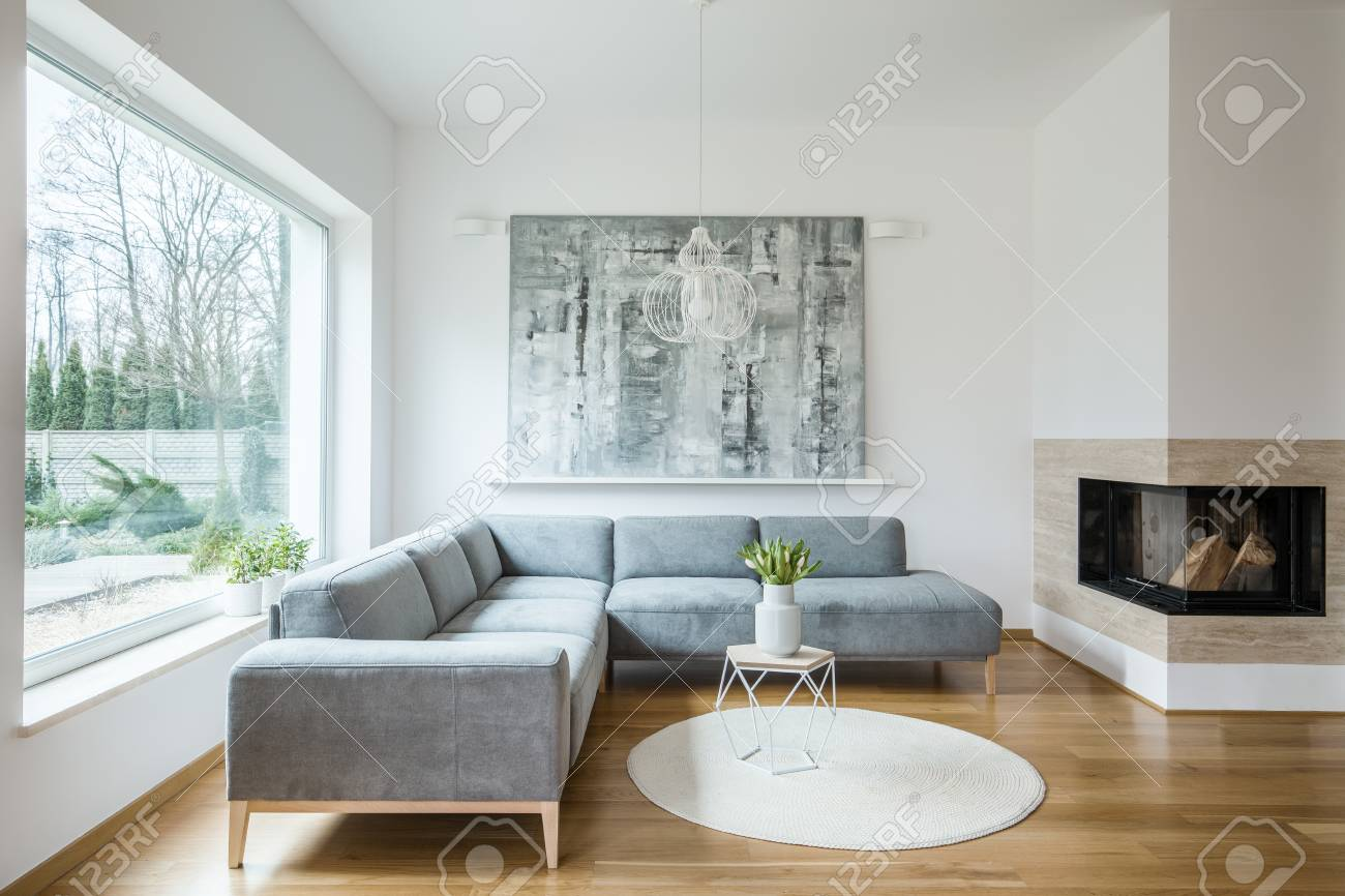 Fireplace next to a grey corner sofa and table with tulips against..