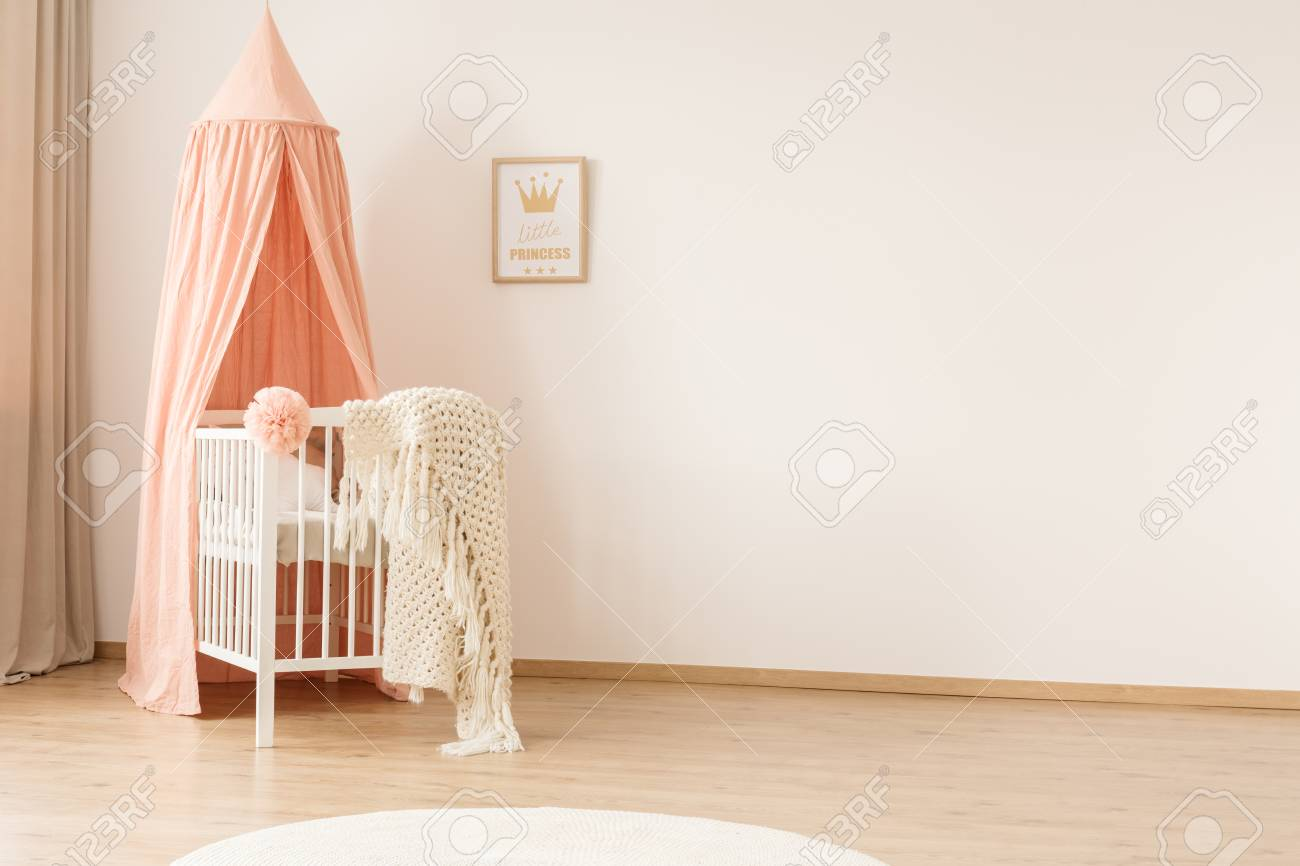 White woolen blanket and pastel pink pompom placed on a wooden crib with canopy in bright baby room interior with poster on the wall - 101692933
