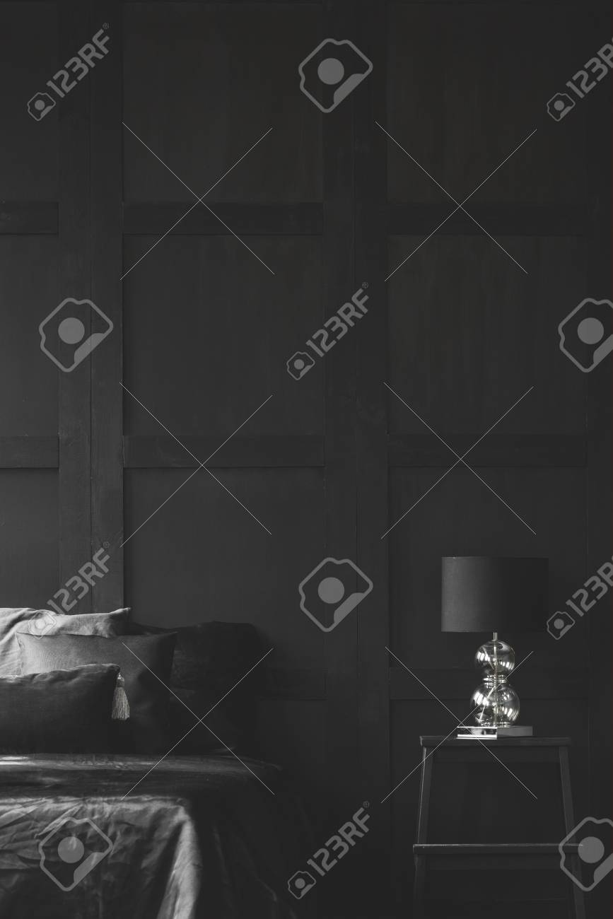 Lamp On Table Next To Bed In Dark Black Bedroom Interior With