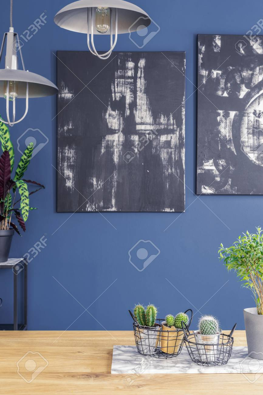 Black paintings on a blue wall and industrial pendant lights..