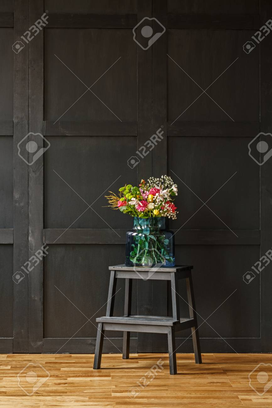017001e1 A rich colorful bouquet of beautiful summer flowers in a blue glass vase on  a black