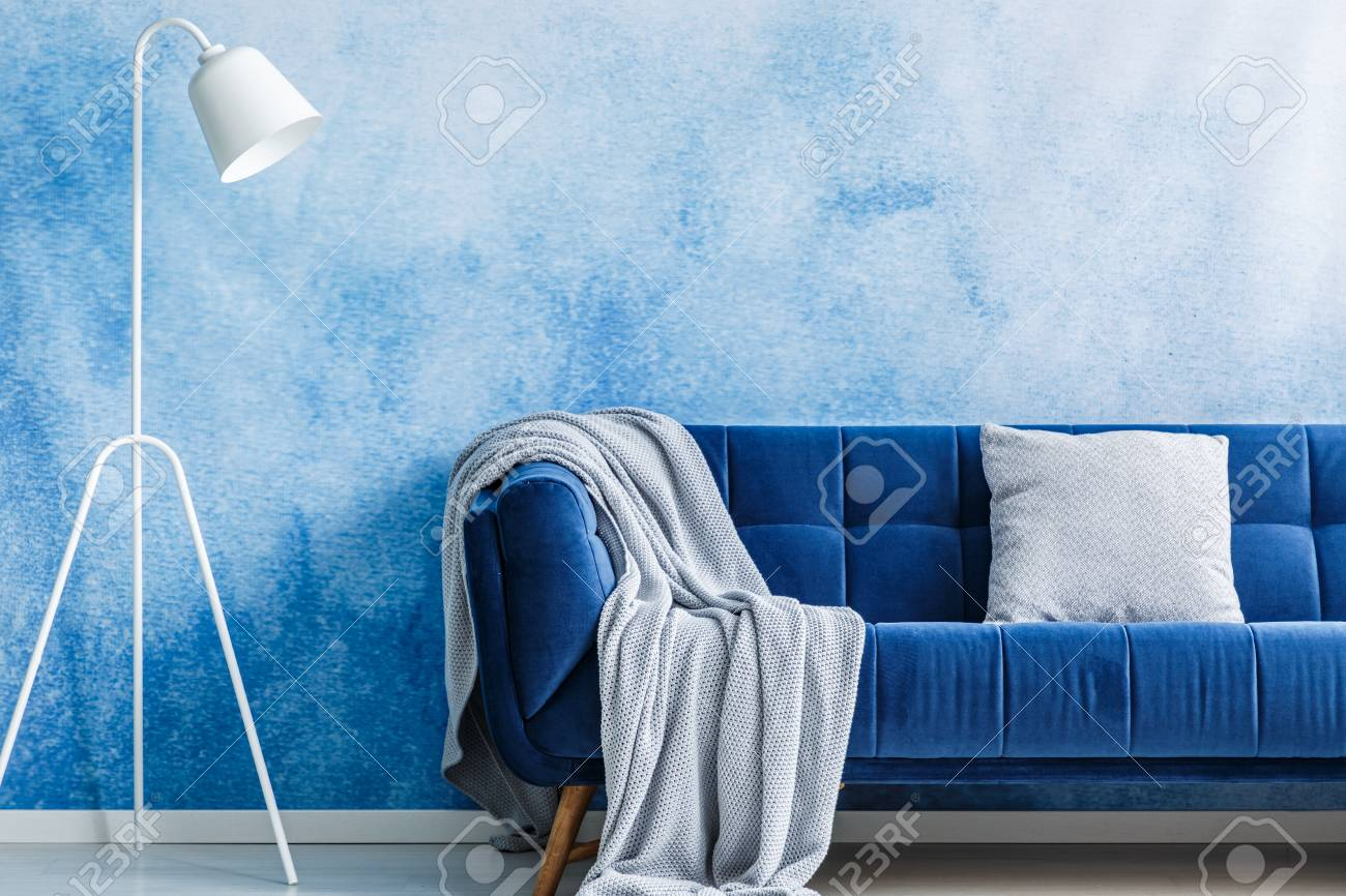 Navy Blue Sofa With Blanket And Pillow Lamp Set On An Ombre