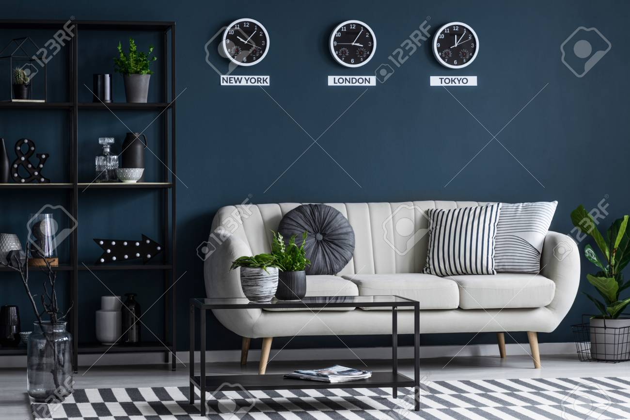 Picture of: Black Table Near Beige Sofa Against Navy Blue Wall With Clocks Stock Photo Picture And Royalty Free Image Image 102145725