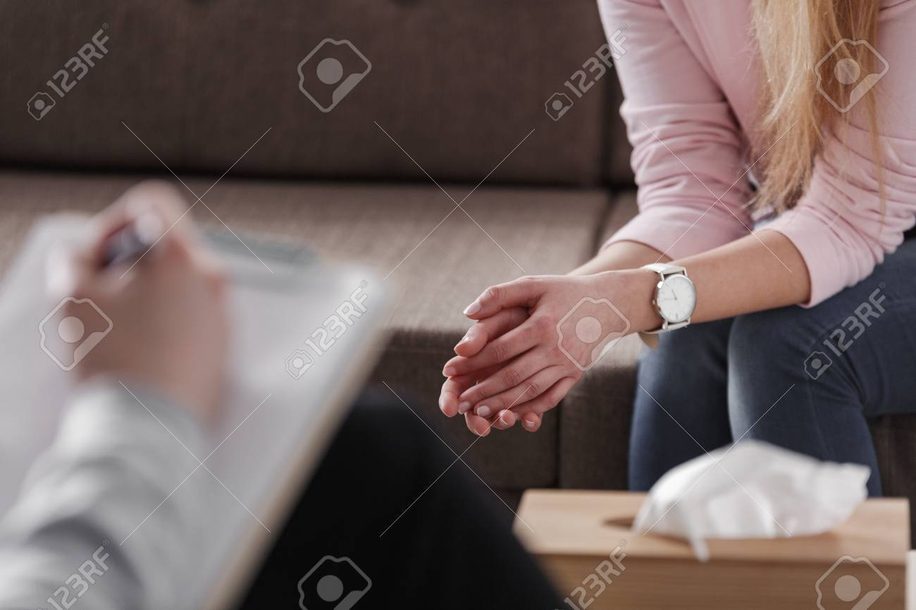 Close-up of woman's hands during counseling meeting with a professional therapist. Box of tissues and a hand of counselor blurred in the front. - 102078135