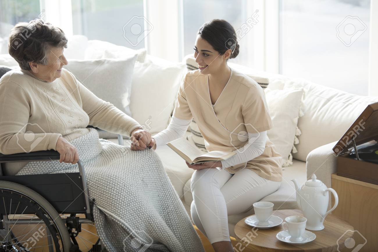 A disabled old woman in a wheelchair holding the hand of a tender professional medical assistant during tea time in a living room of luxury retirement home - 102549506