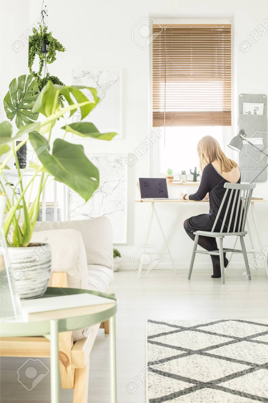 photo blonde girl sitting by the study corner desk with lamp and laptop in white living room interior with
