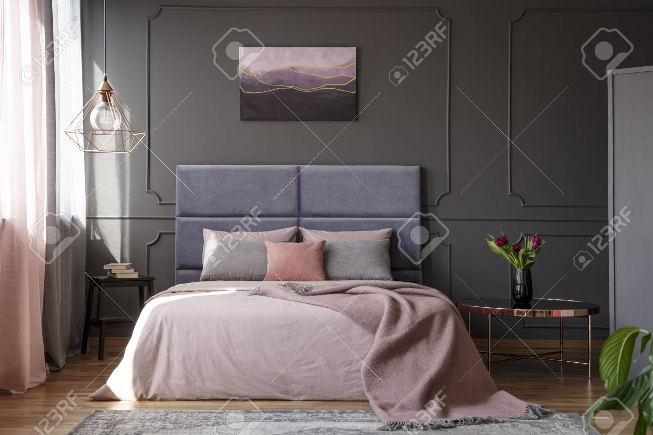 Tulips on copper table next to pink bed against grey wall with molding with poster in bedroom interior - 102519824