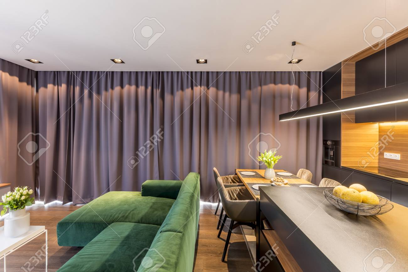 Green corner sofa in grey apartment interior with kitchen island..