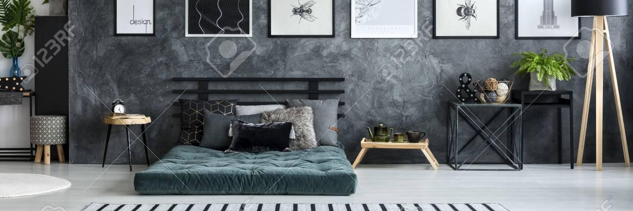 Simple posters hanging on texture wall in dark grey bedroom interior..