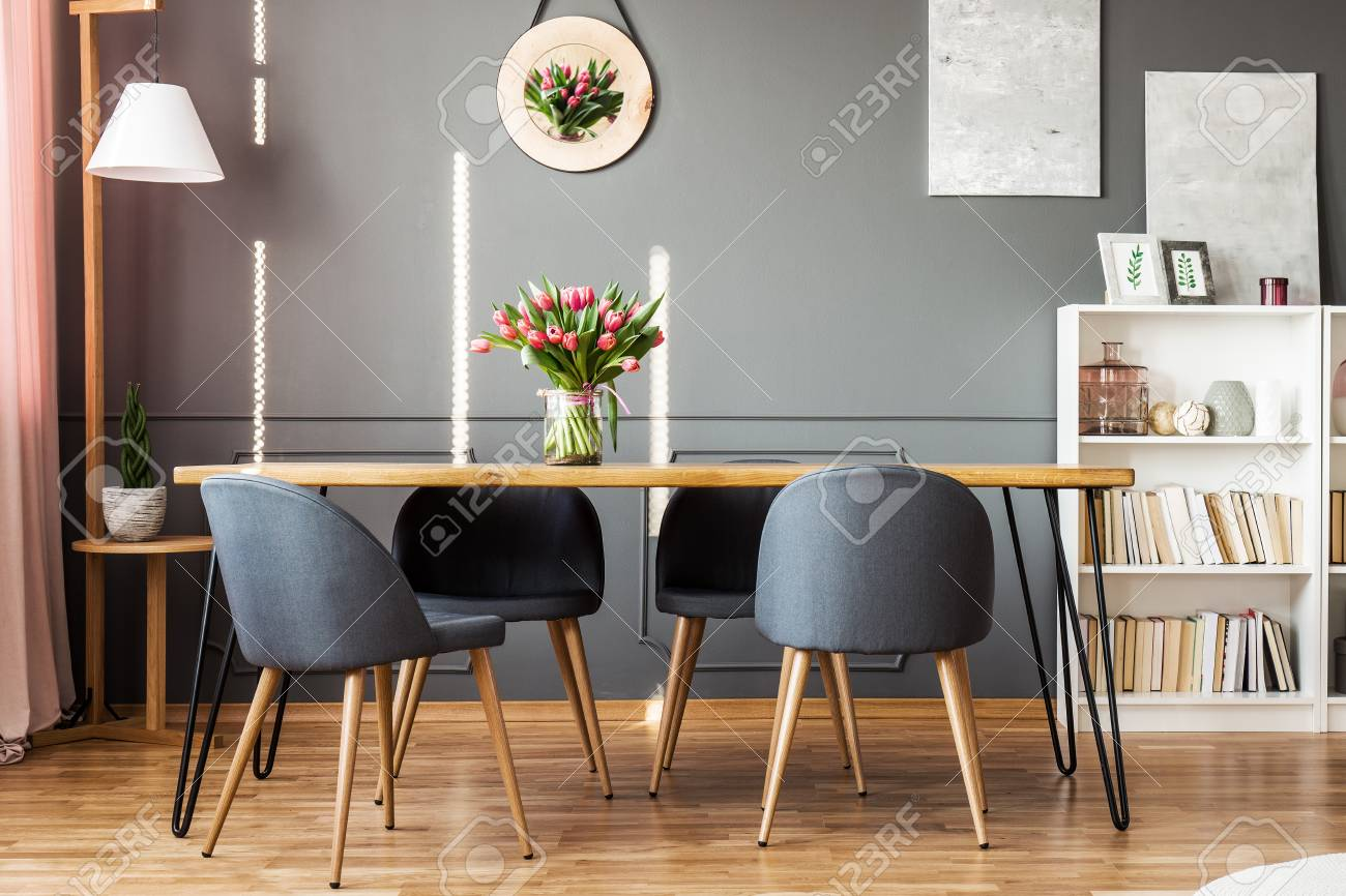 Stock Photo   Wooden Dining Table, Grey Chairs, Bookshelf And Pink Tulips  In Dining Room Interior
