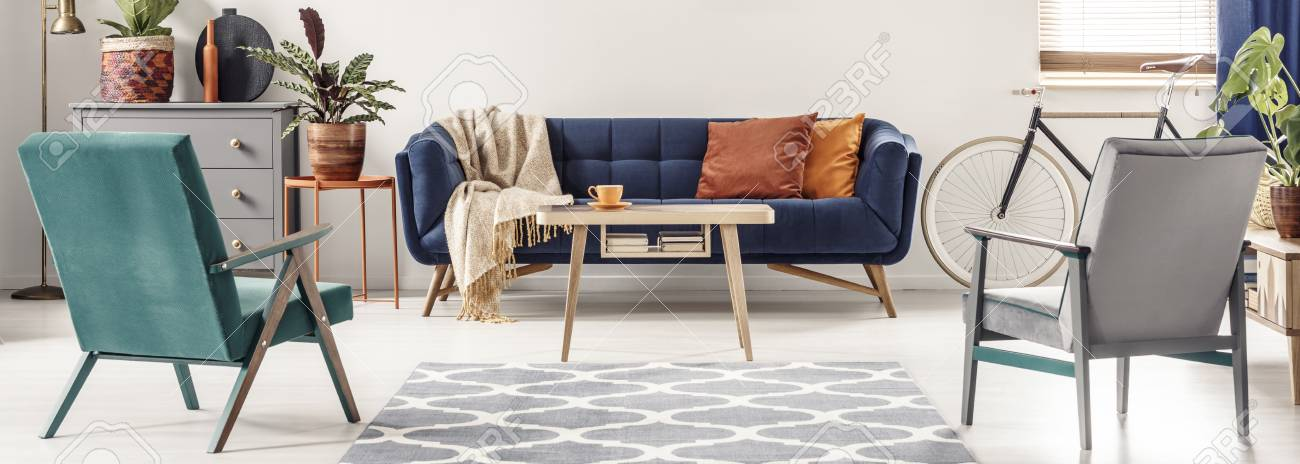 Real photo of green and gray armchairs standing next to a patterned rug, facing a blue sofa with orange pillows and a wooden table in colorful living room interior - 103267043