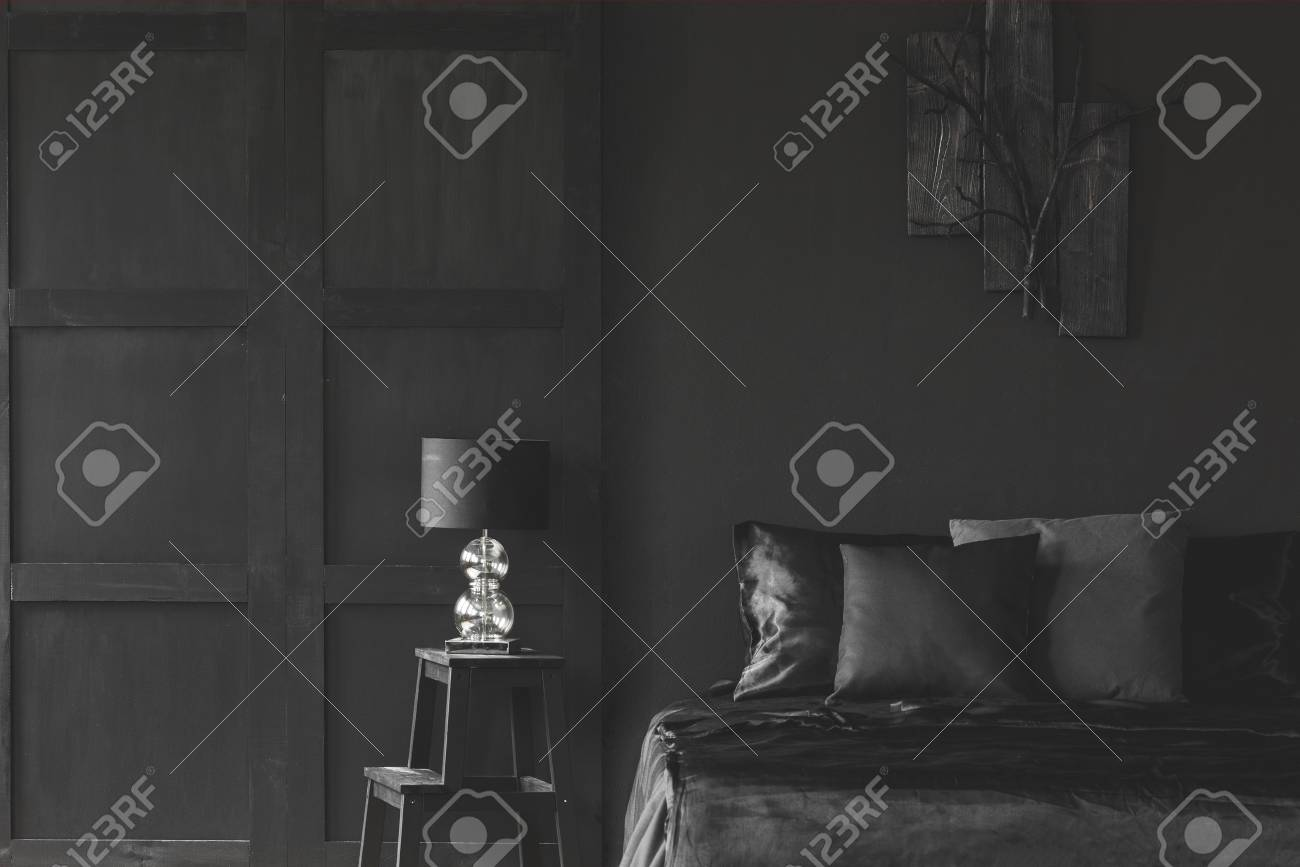 Lamp On Stool Next To Bed In Dark Black Bedroom Interior With
