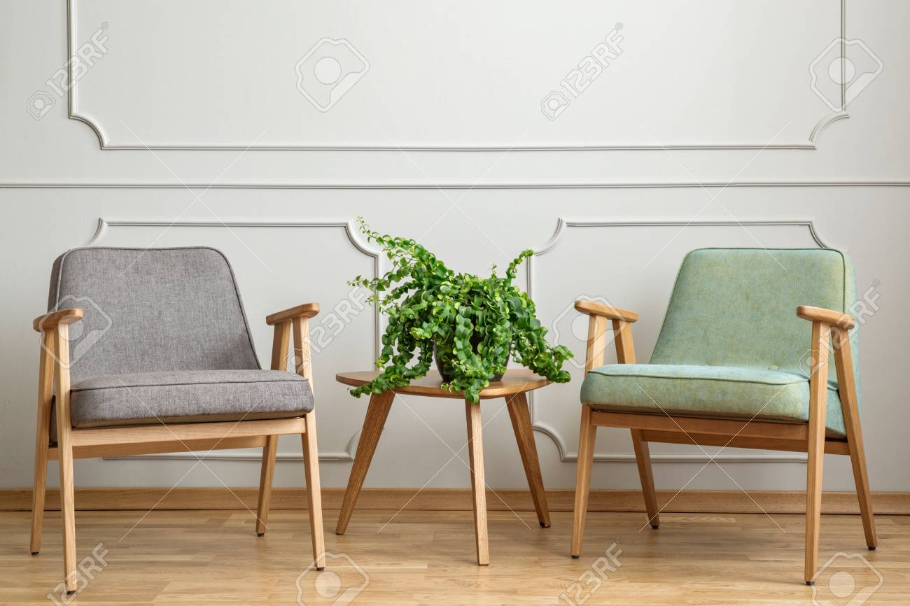 Real Photo Of A Small Table With A Plant Standing Between Two