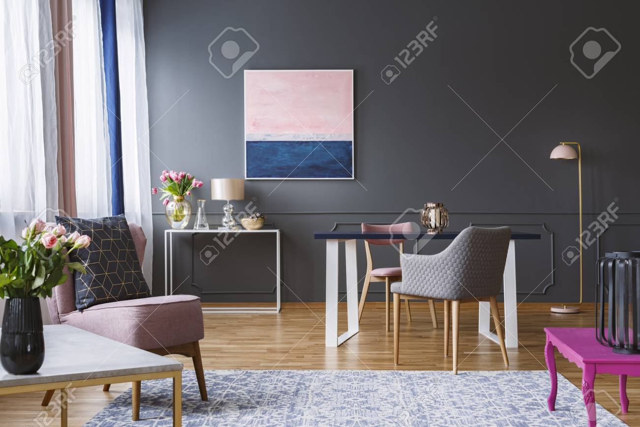 Pink and navy blue painting in grey living room interior with..