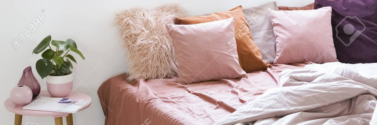 Real Photo Of A Large Bed With Pink Bedding And Pillows Standing