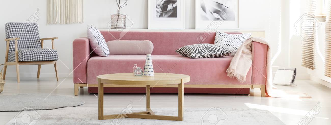 Pink Sofa With Patterned Pillows And Wooden Coffee Table With ...