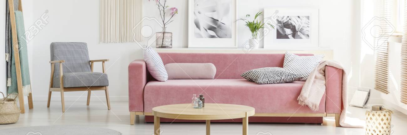 Patterned Armchair Next To A Pink Sofa With Pillows, Round Table ...