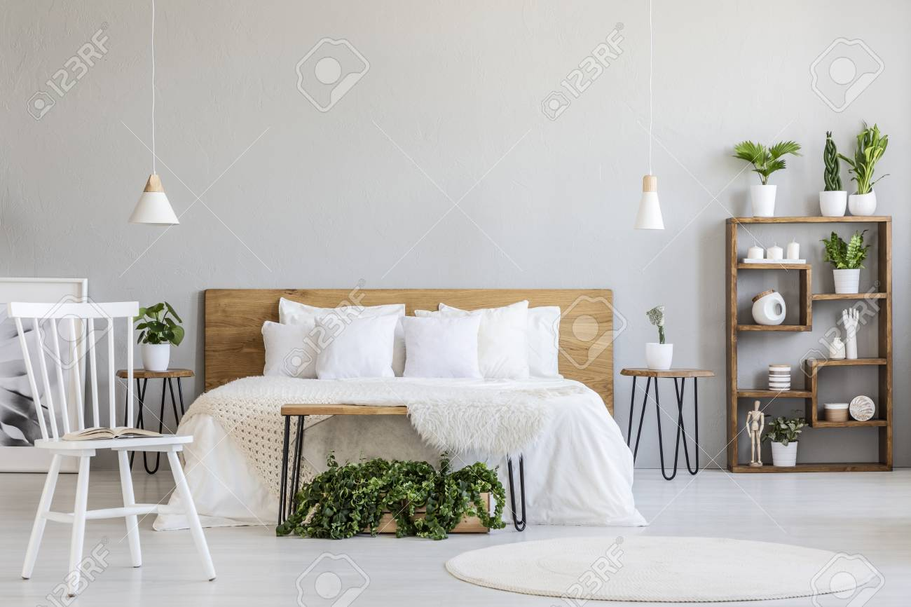 White Chair Near Bed With Wooden Headboard In Bright Bedroom Stock Photo Picture And Royalty Free Image Image 105286359