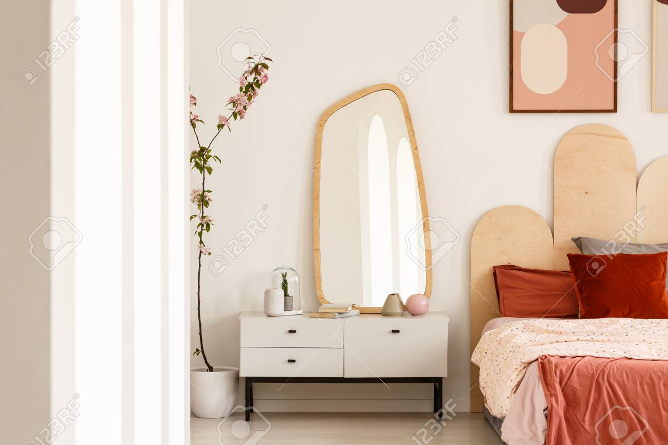 sports shoes c0712 48236 Plant next to white dressing table with mirror in red bedroom..