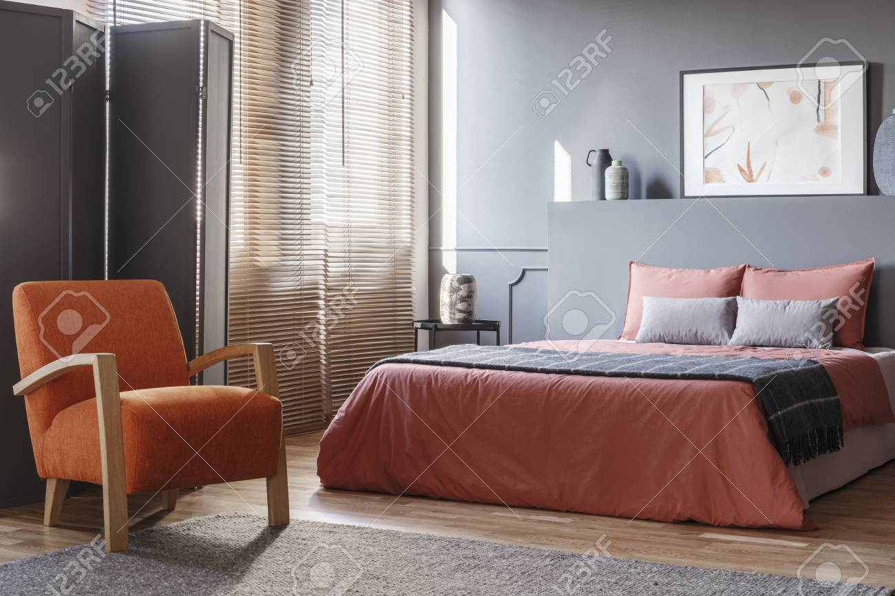 Orange armchair next to pink bed in modern grey bedroom interior..