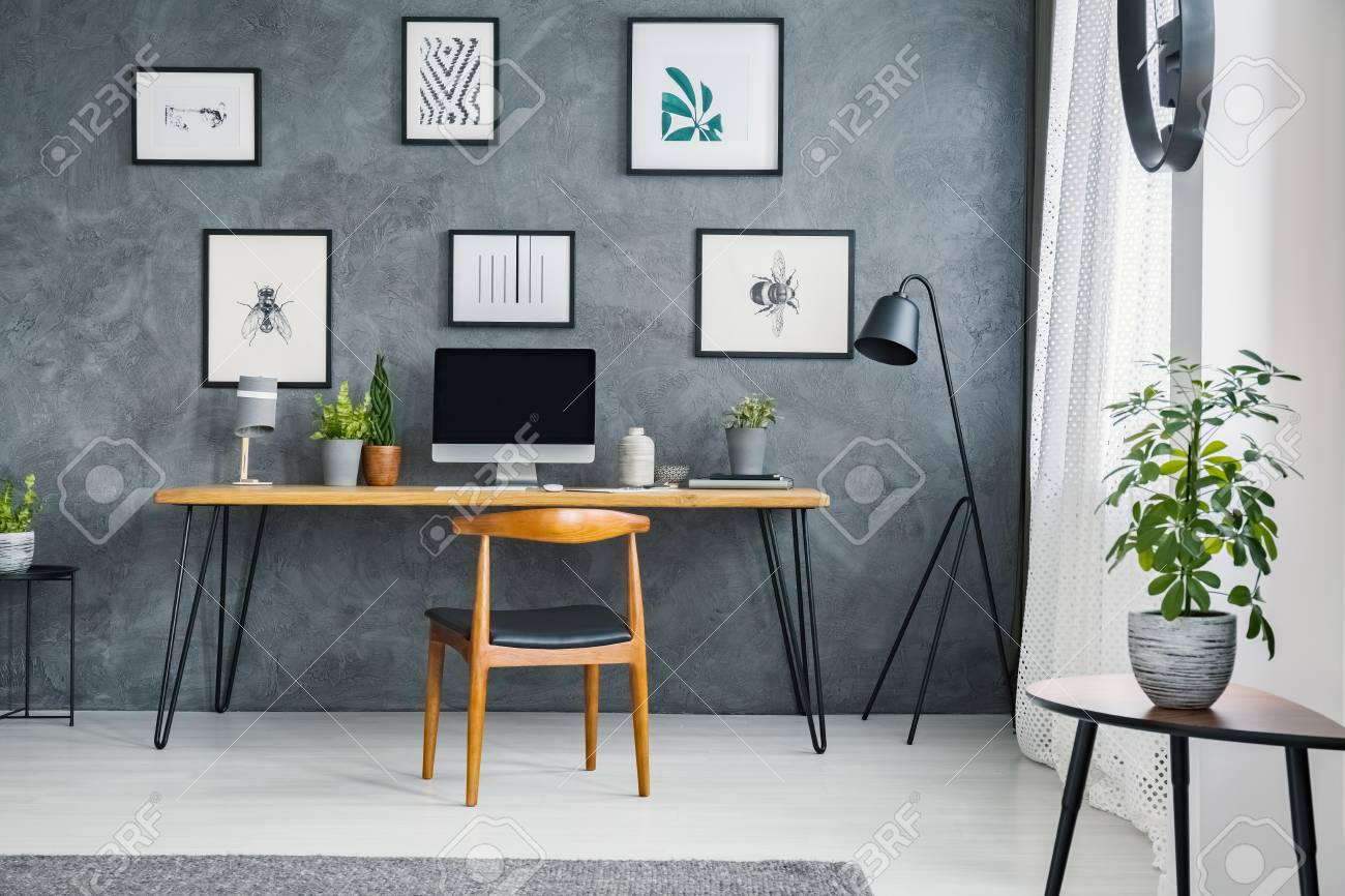 Plant On Table Near Wooden Chair At Desk With Desktop Computer