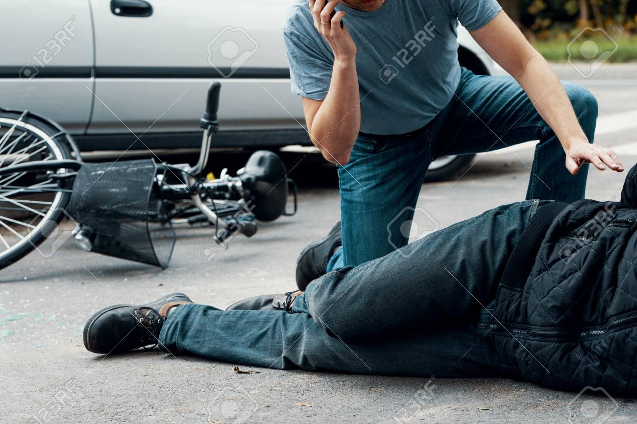 Man calling an ambulance for a victim of a car crash