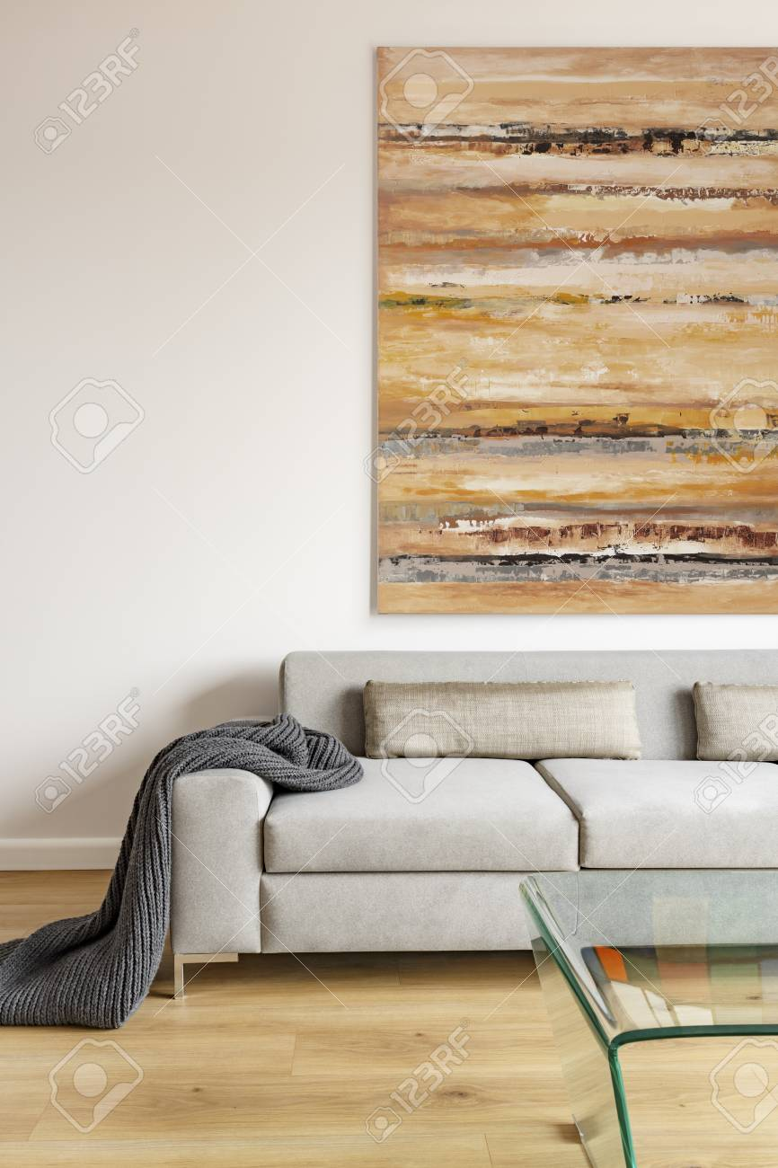 Blanket on beige settee under colorful painting in modern living room interior. Real photo - 105970420