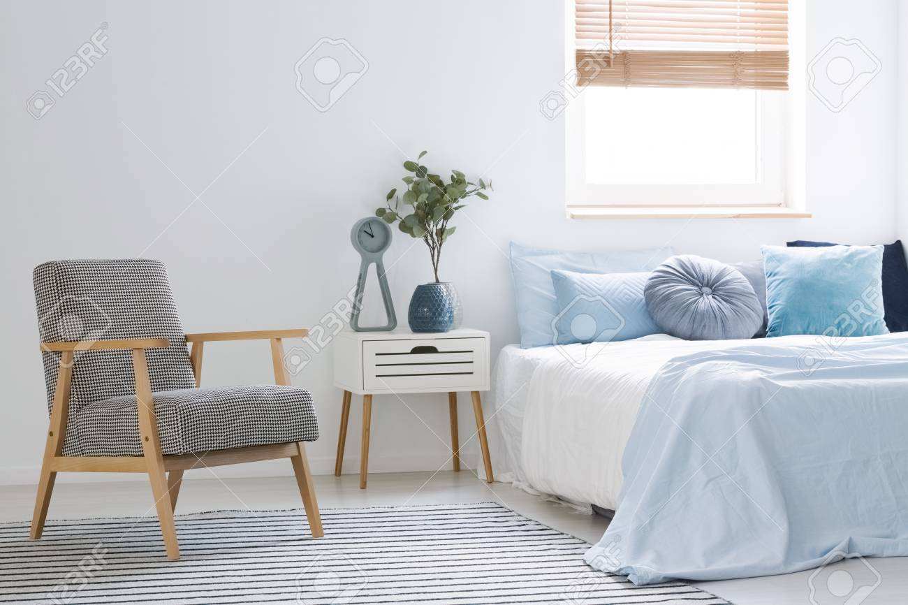Armchair Standing On Striped Carpet In White Bedroom Interior With Bed With  Blue Sheets And Many