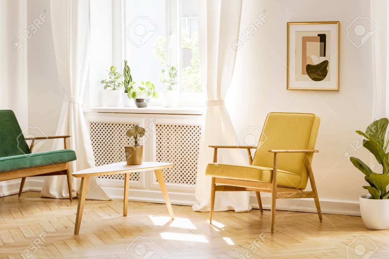 photo yellow retro armchair and a green sofa by a big sunny window in a stylish white living room interior