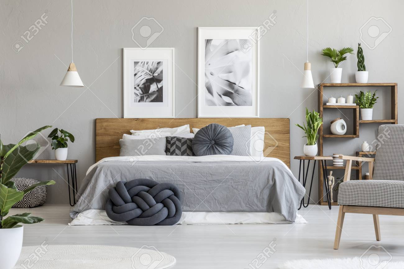 Posters Above Wooden Bed In Grey Bedroom Interior With Plants