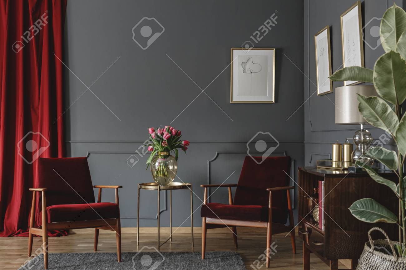 Stock photo two burgundy armchairs placed in grey living room interior with red drape molding on the wall with posters fresh flowers in glass vase and
