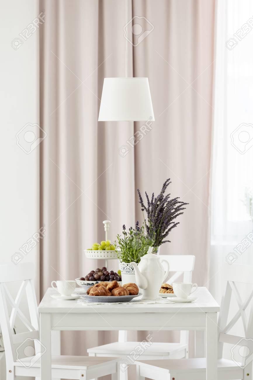 Lámpara sobre la mesa blanca y sillas en comedor interior de comedor con  plantas y real foto exterior
