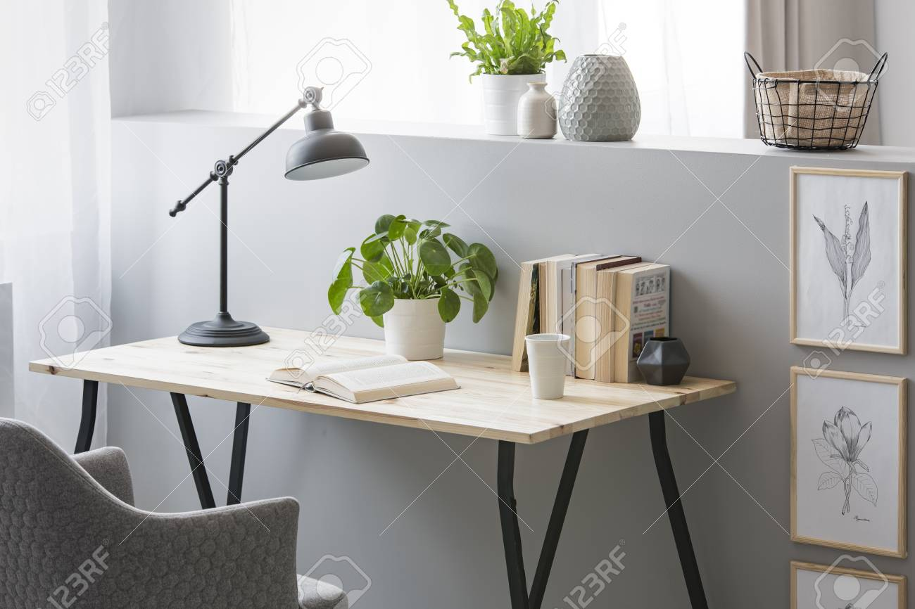 Real photo of wooden desk with fresh plant, black lamp, coffee cup and books standing on half-wall with simple posters - 107030662
