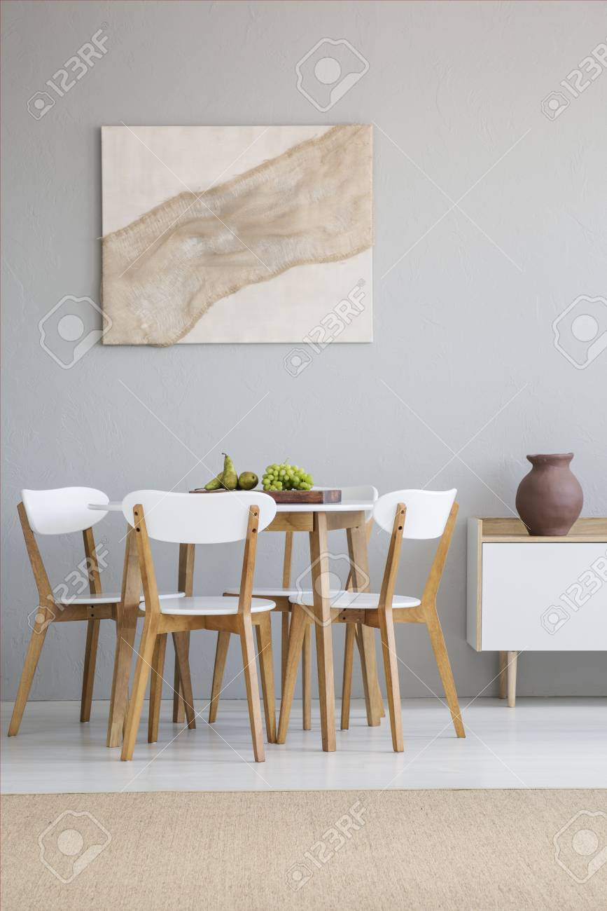 Real photo of a natural, scandi dining room interior with a round, wooden table and white chairs standing against light gray wall - 107030870